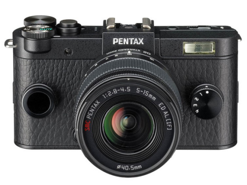 Black Pentax Q-S1: frontal view of compact system camera with lens, aspect ratio two wide by one high; two dials either side of the lens and Pentax written in white above lens mount