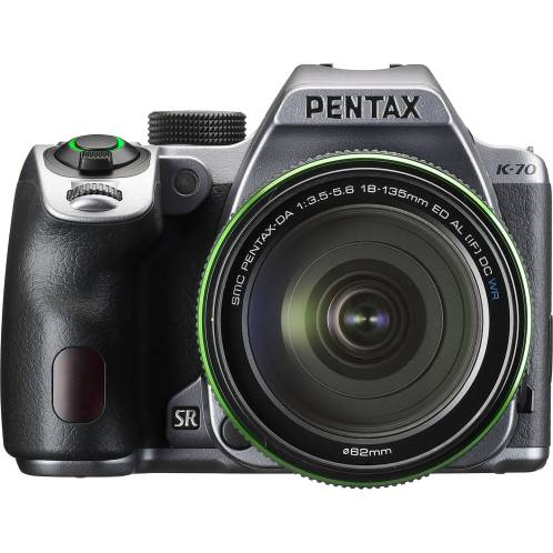 SLR camera with grey top plate and lens without hood, photographed facing the camera. Green LED illumination around shutter button indicates camera is switched on.