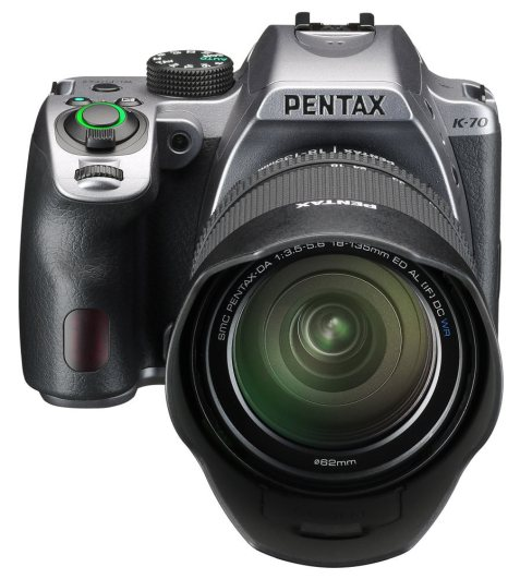 SLR camera with grey top plate, otherwise black and with a lens and lens hood, facing front.