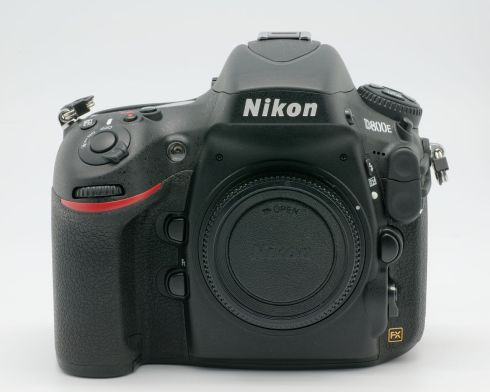 Frontal product photo of a black camera against blueish white background.